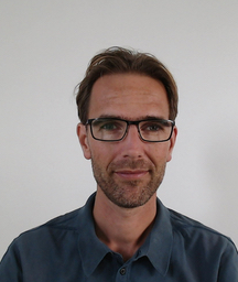 Joost Jager is wearing glasses and a shirt against an off-white grey background